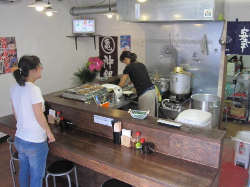 カウンター内の厨房で忙しく調理するスタッフ