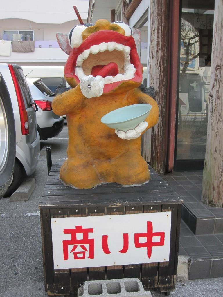 沖縄そばを食べるキャラ化されたシーサー
