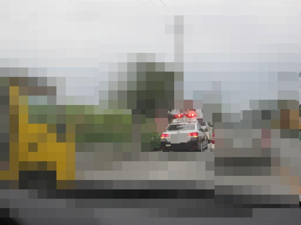 道路の路肩で赤色灯(パトライト)が光り違反切符を切られるドライバー