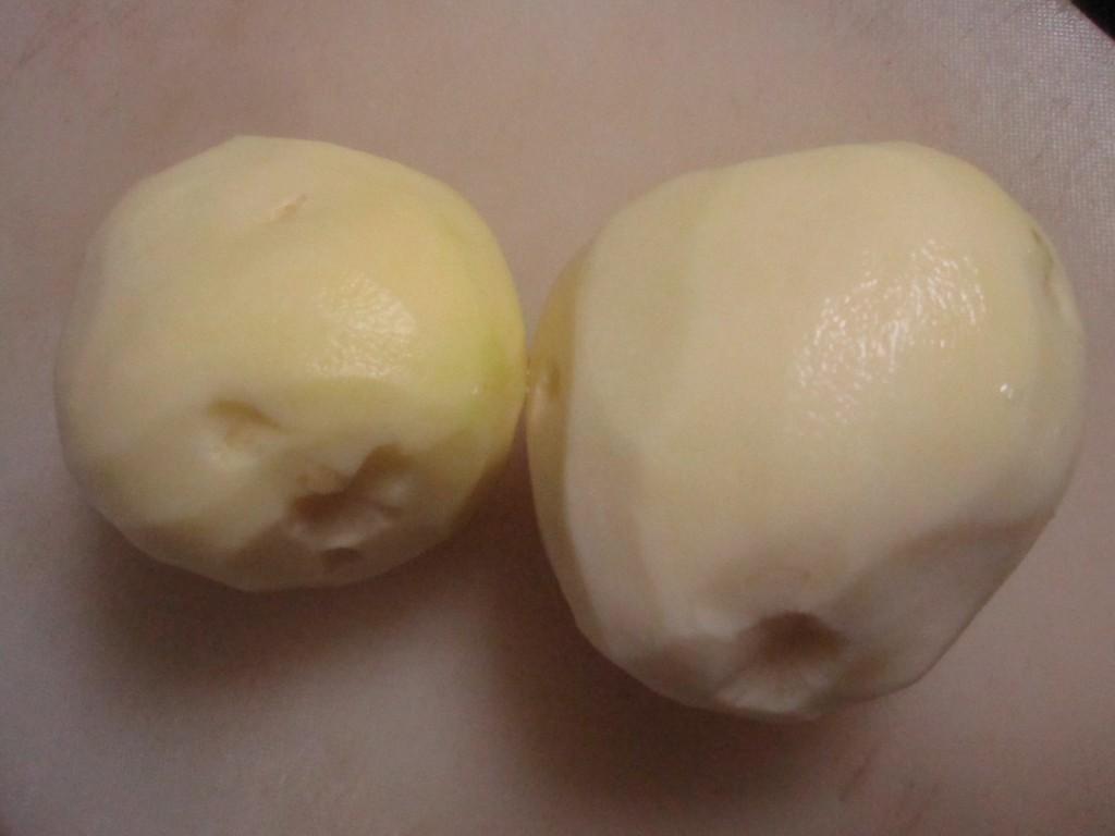 まな板の上の洗って皮をむいたジャガイモ