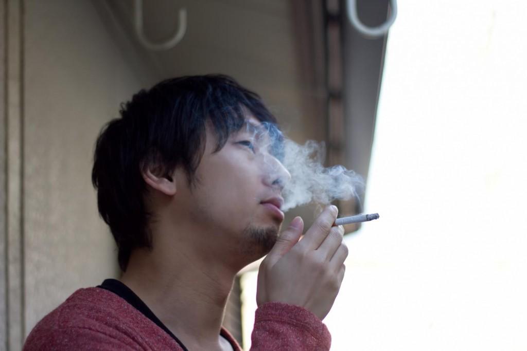 ベランダで煙草(タバコ)を吸う男性