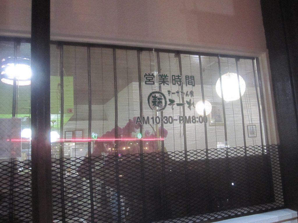 店舗外観:店内からの明かりで透ける窓に営業時間が記載されている