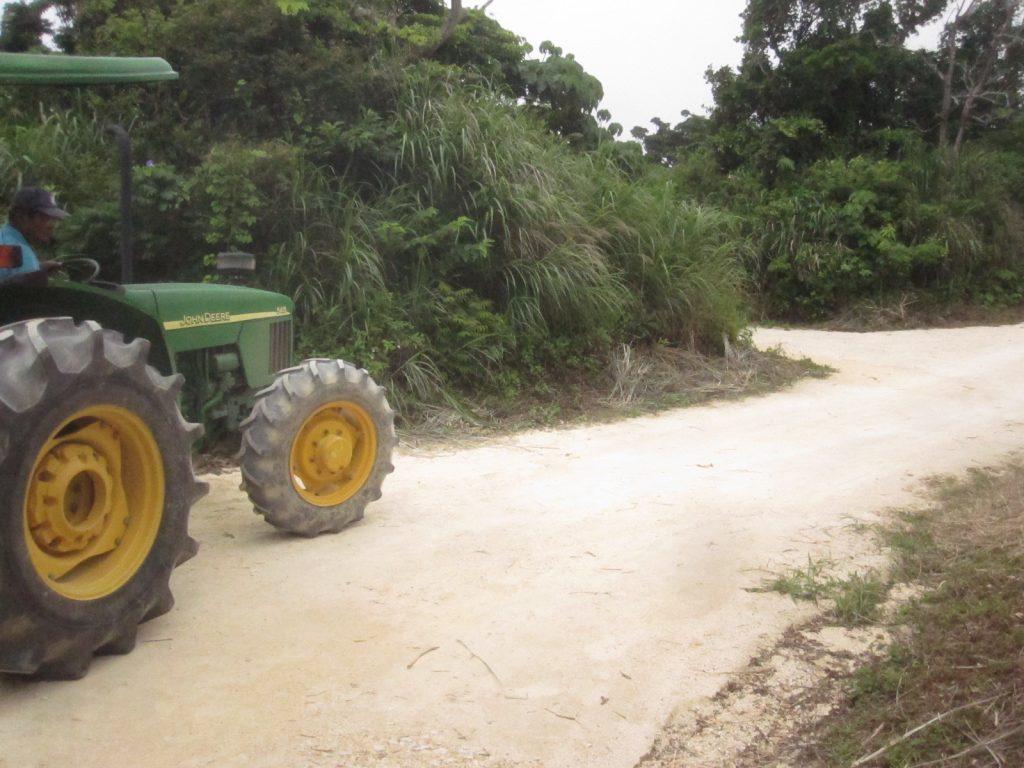 ゆっくりと狭い道路を突き進むトラクターバス