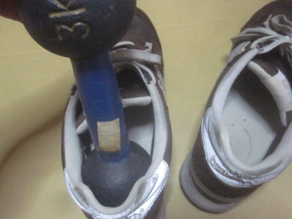 接着剤でソール剥がれを修理した左の靴に重しのダンベルを履かせる