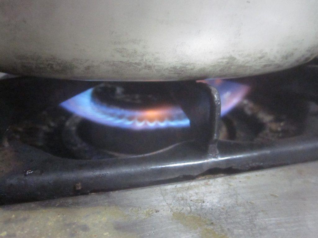 ガスコンロに点火し鍋で水を沸騰させる