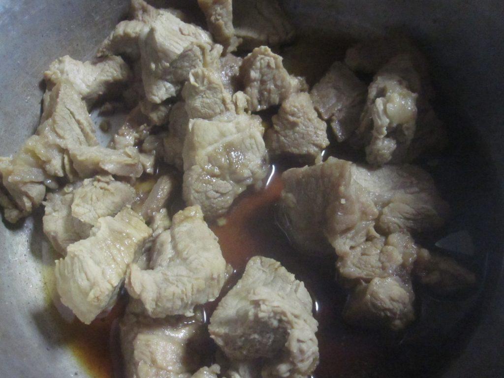 豚の三枚肉を鍋に移して味付けをする