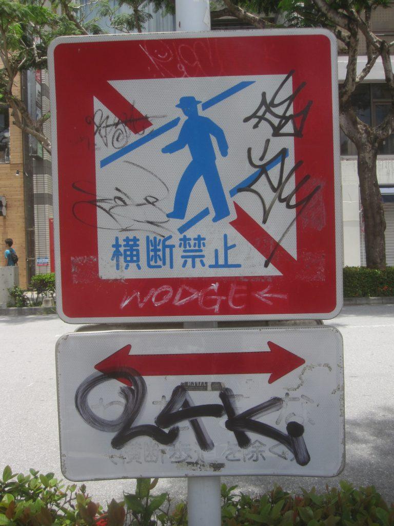 観光客がスプレーやマーカーで落書きされた交通標識を見ていたが沖縄県民として恥ずかしい