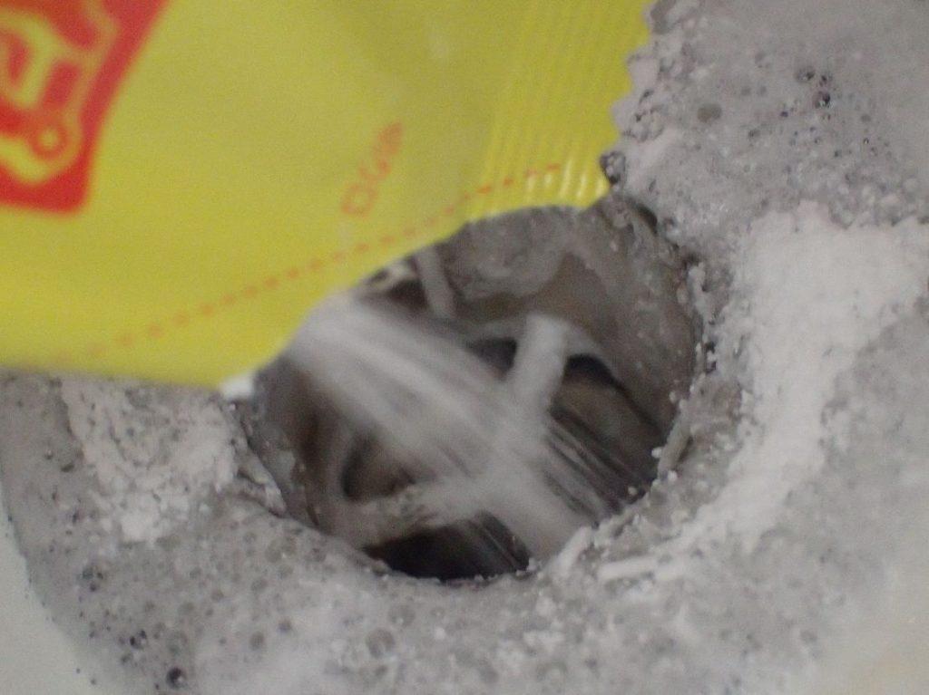 汚臭・悪臭を放つ排水口に粉末タイプのパイプユニッシュを投入する瞬間!
