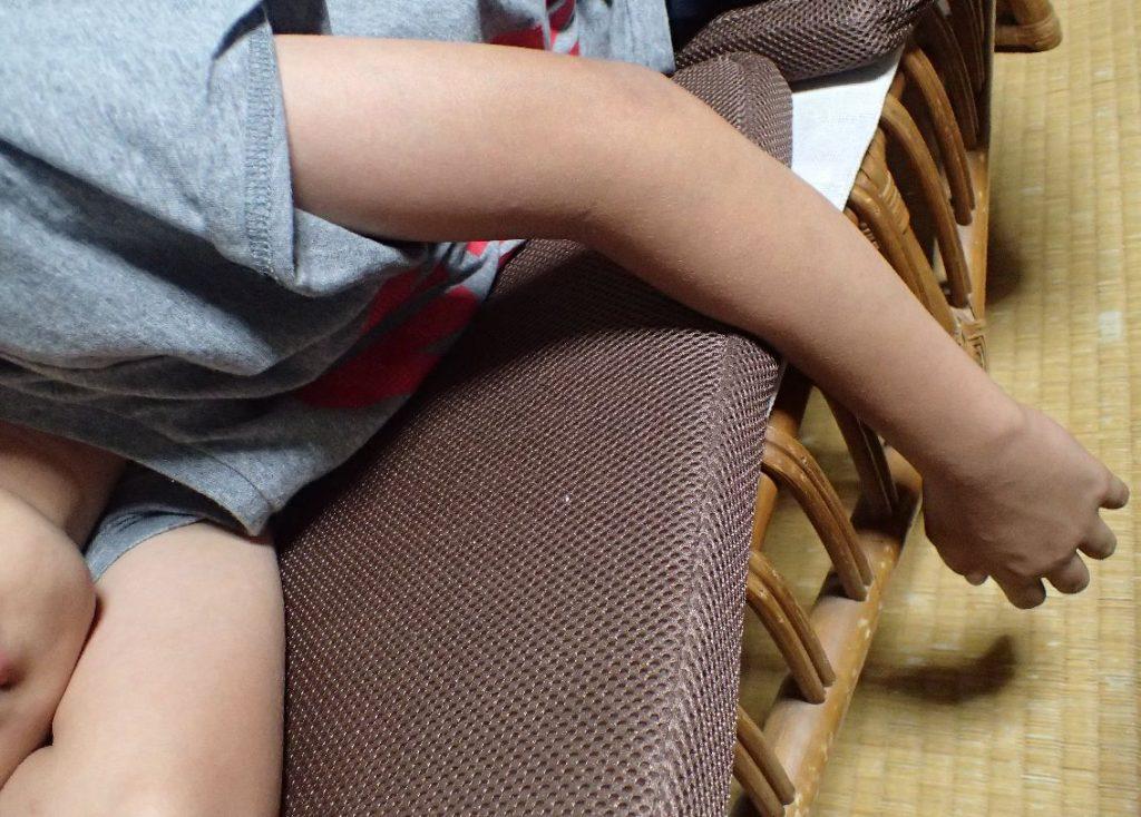 腕枕したままで寝ている少年の写真