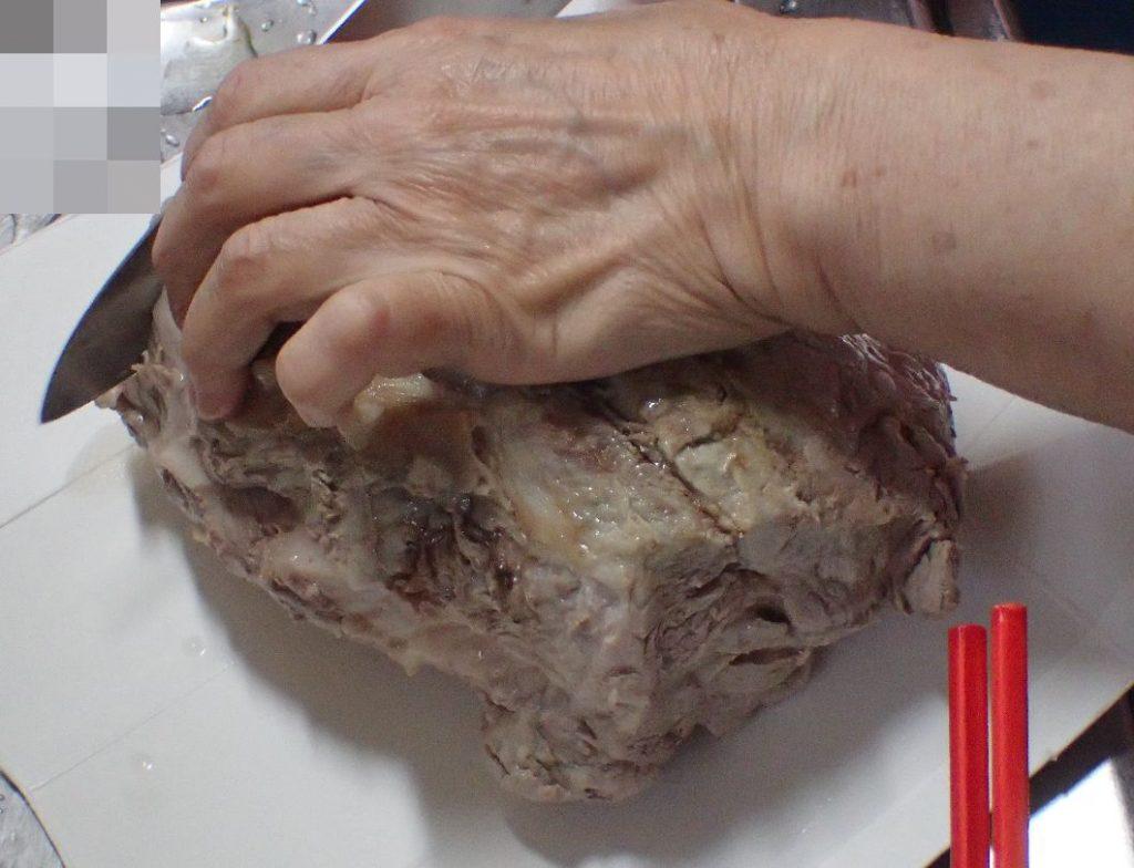 豚肉ブロックを牛乳パックまな板の上で切る様子