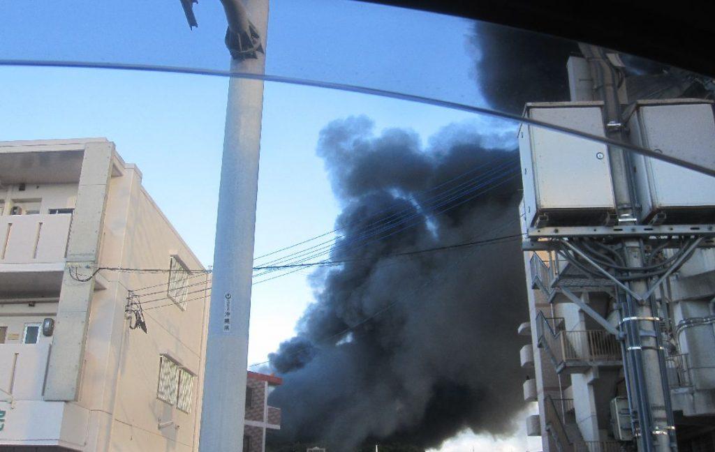 アパートの間から黒煙が空へ上がる異様な光景