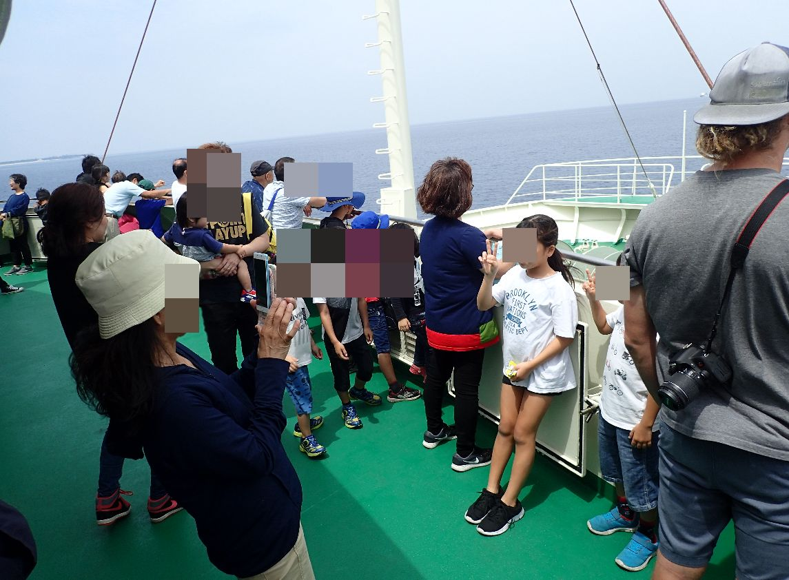 海の上・船の上で記念撮影する家族・観光客の姿