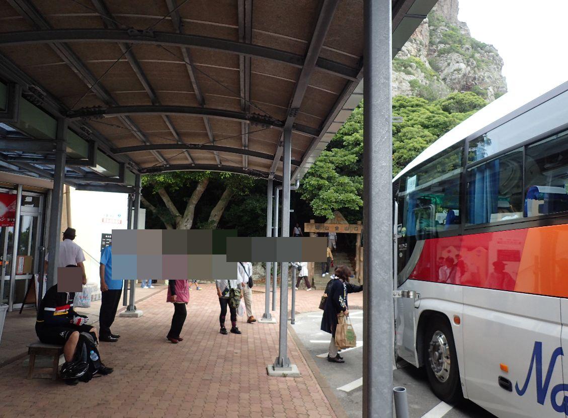 城山お土産品店の前で観光バスが止まり乗客が降りていく