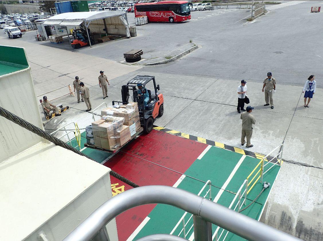 フォークリフトで荷物を運び込む港員