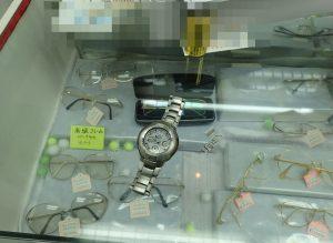 時計屋さんで職人に壊れたバックルを見せる様子