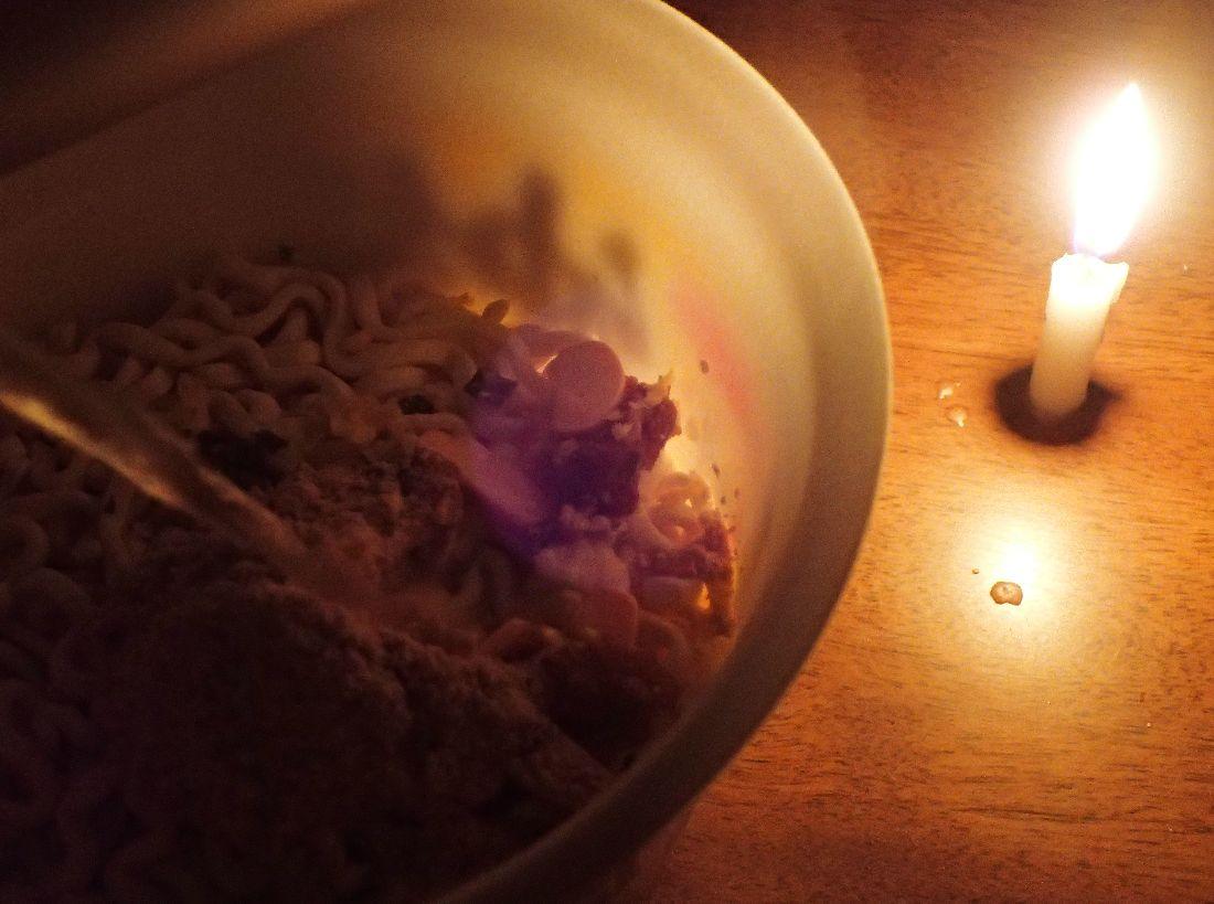 台風の停電の中、ロウソクの明かりでカップラーメンに湯を注ぐ